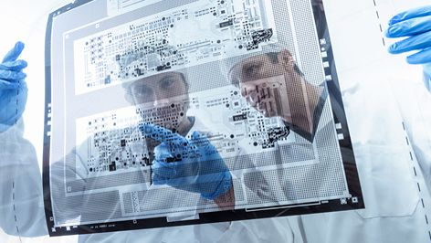 Workers inspecting circuit board negative sheet in circuit board factory