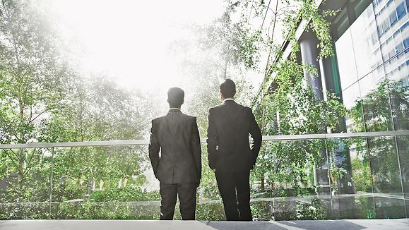 Two business men standing in green office building looking at the sun