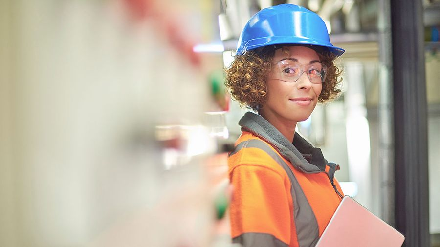 A female industrial service engineer has just conducted a safety check of a control panel in a boiler room.