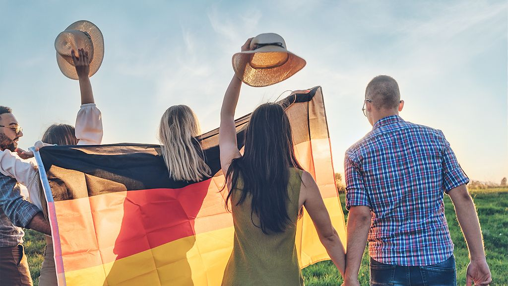 Group of young handsome people spreading wide german flag at sunset.