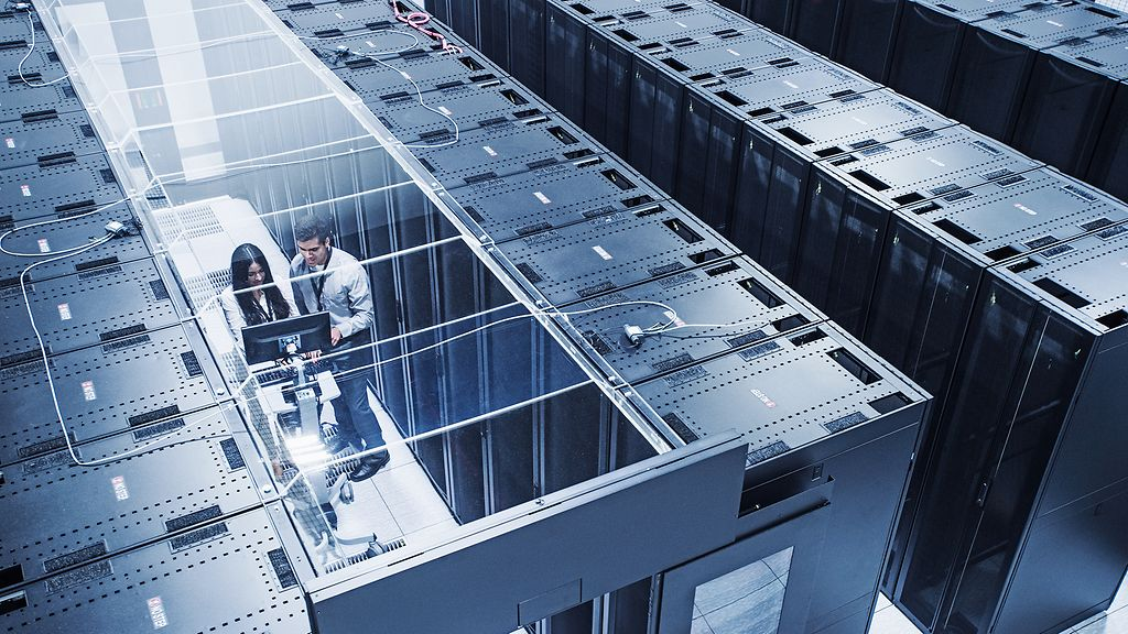 A typical data center could supply around 150 households with heat. High angle view of technicians working in server room.