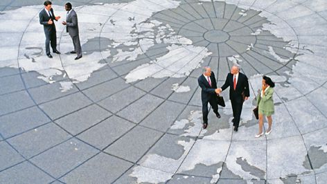 Businesspeople stand on worldmap