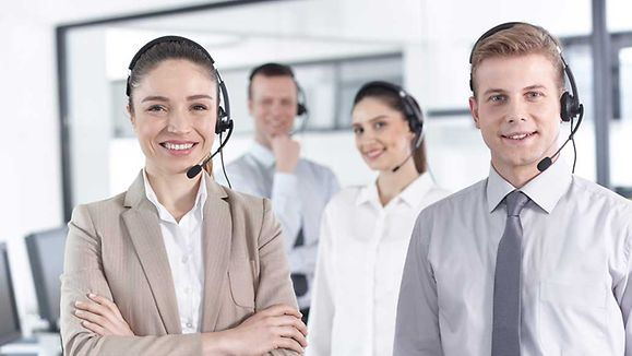 Group of happy, cheerful call center workers are smiling and looking at the camera