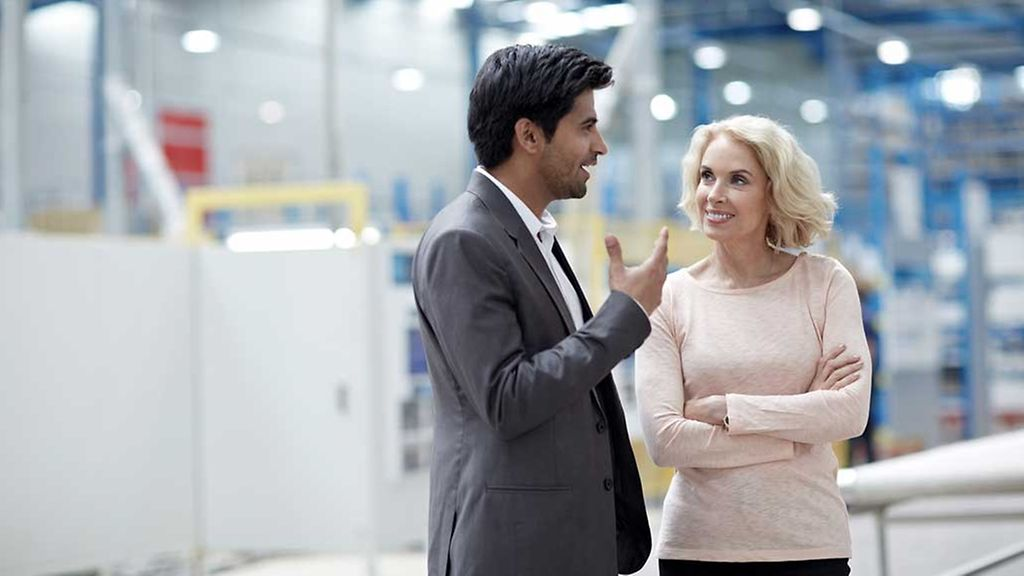 Young businessman having a conversation with senior female colleague at factory shopfloor